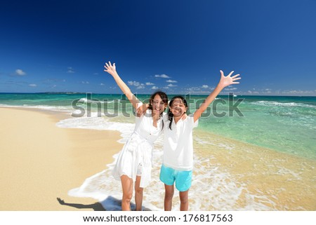 Parent and child playing at the beach - stock photo