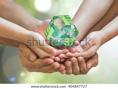 Parent and children holding together recycled green leaf sign planet on person hands on blur nature greenery background sun flare: Environment CSR ESG concept. Elements of this image furnished by NASA - stock photo