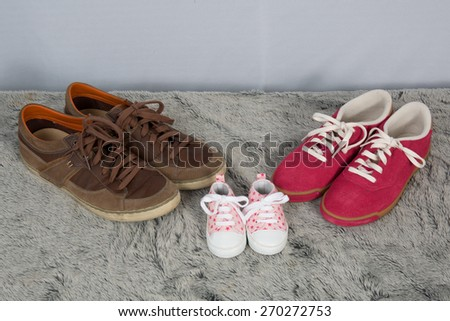 Parent and new born child shoes on the floor - stock photo