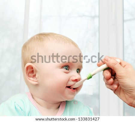 Parent feeding Hungry Baby in home interior - stock photo