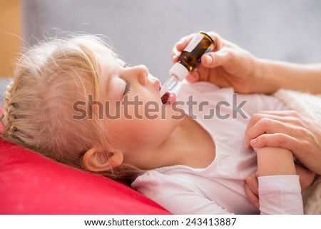 Parent giving medicine drops to her sick child - stock photo