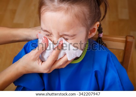 Parent hand helping the playing little girl to blow her nose with a hygienic wet wipe. Seasonal sickness. - stock photo