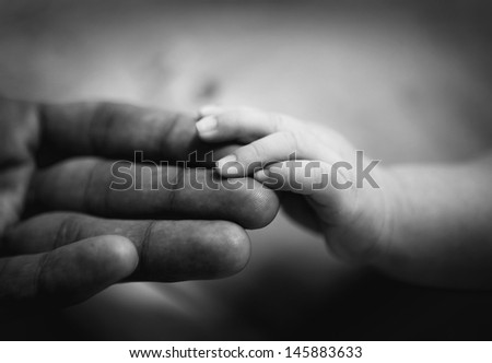 parent holding newborn baby hand. family concept. black and white  - stock photo