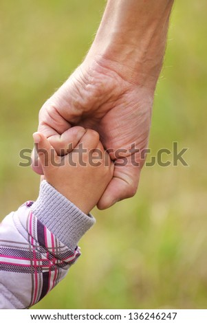 parent holds the hand of a small child - stock photo