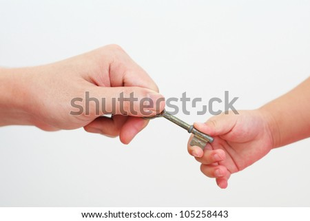 Parent passing down house key to child, on white background - stock photo