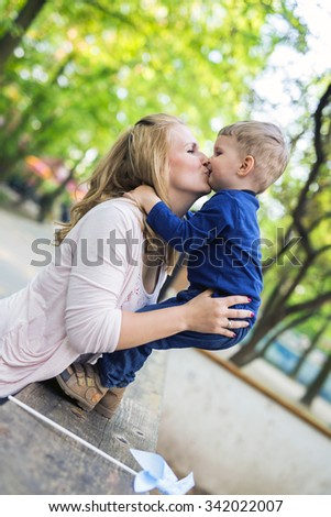 Parent touching noses with her son and smiling happily - stock photo
