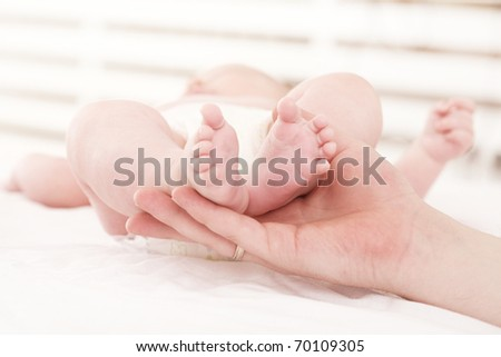parental hand holds legs of the baby - stock photo
