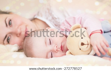 Parenthood. Motherhood.Young mother and her baby, sleeping in bed - stock photo