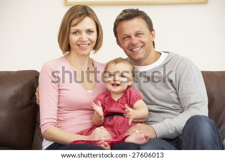 Parents And Baby Daughter On Sofa - stock photo