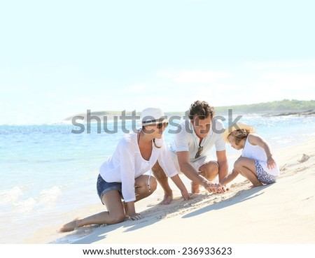Parents and child playing on a sandy beach together - stock photo