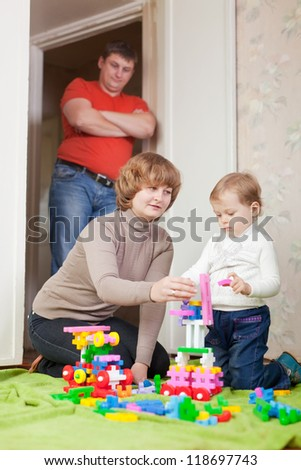 parents and child plays with set in home - stock photo