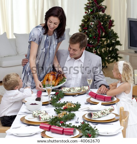 Parents and children in Christmas dinner with turkey at home - stock photo