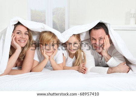 Parents and children laying in bed in the morning - stock photo