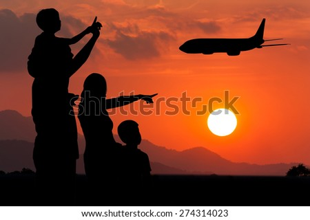 Parents and children look at the airplane on the sky at sunset - stock photo