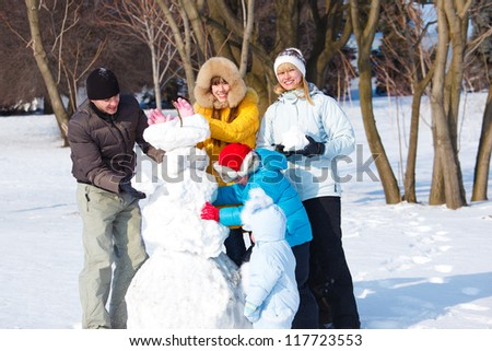 Parents and children playing with snow - stock photo