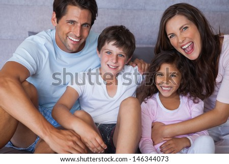 Parents and children smiling at camera and sitting on bed - stock photo