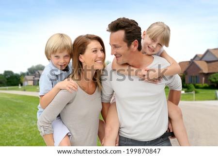 Parents and children standing in neighborhood - stock photo