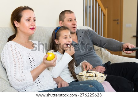 Parents and cute girl watching TV show and smiling indoors. Focus on woman - stock photo