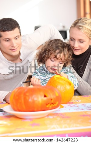 Parents and daughter in the kitchen preparing pumpkin - stock photo