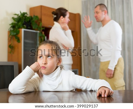 Parents and daughter quarrel in home. Focus on girl  - stock photo