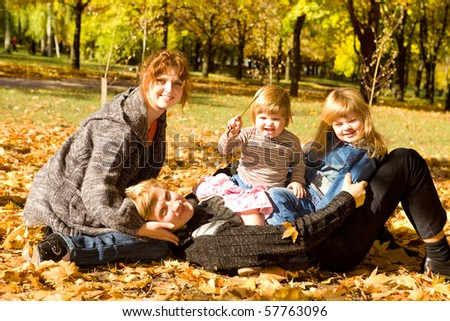 Parents and daughters in autumn park - stock photo