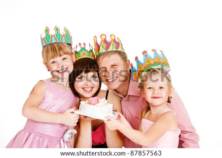 Parents and daughters in party crowns holding birthday cake - stock photo