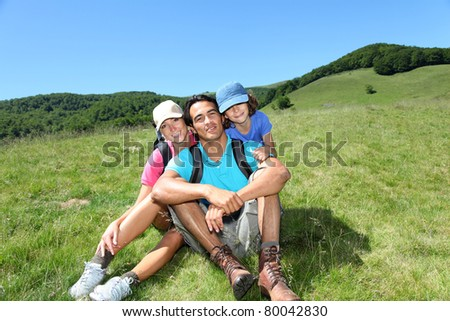 Parents and kid on a hiking day in mountain - stock photo