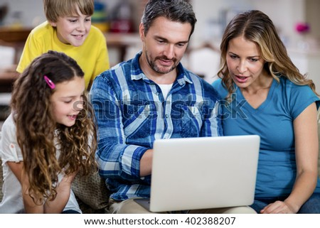 Parents and kids sitting on sofa and using a laptop at home - stock photo