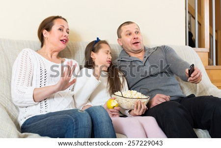 Parents and little daughter watching TV show together at home. Focus on woman - stock photo