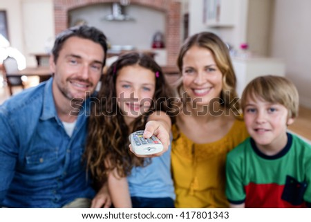 Parents and son watching television in living room at home - stock photo