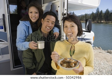 Parents and teenage daughter eating breakfast in RV at lake - stock photo