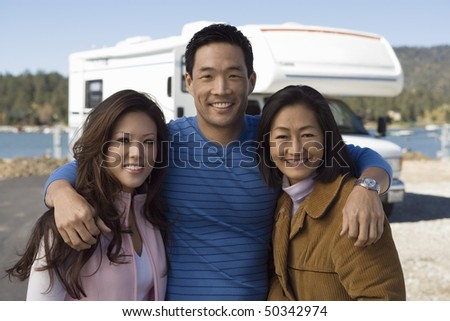 Parents and teenage daughter outside of RV - stock photo