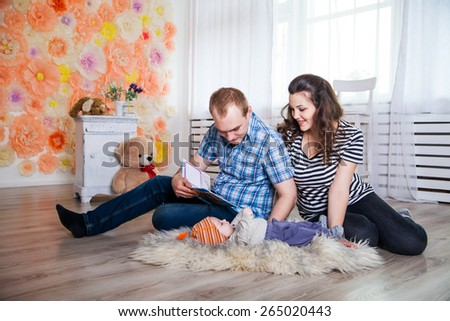parents and their baby lying on the floor and reading book - stock photo