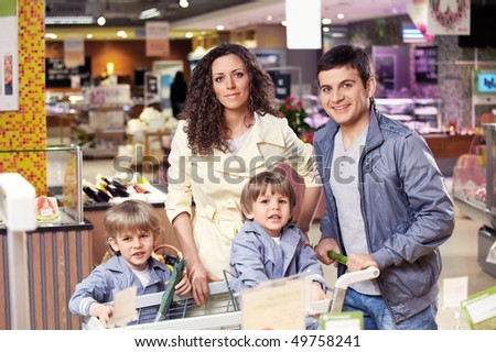 Parents and their children in grocery shop - stock photo