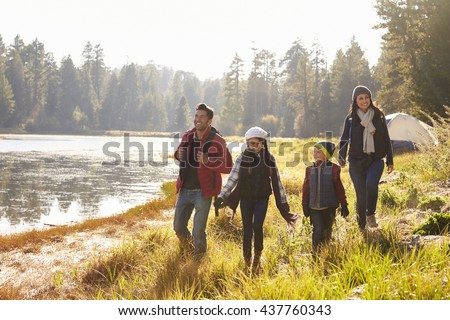 Parents and two children walking near a lake, close up - stock photo