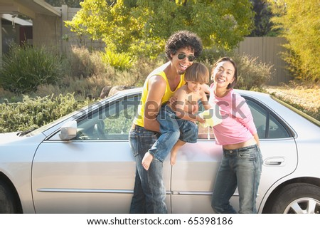 Parents and young son washing car - stock photo