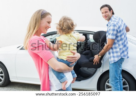 Parents carrying baby and her car seat out of the car - stock photo