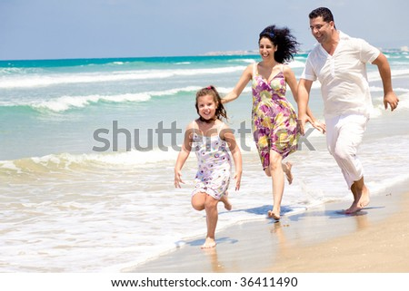 Parents chasing daughter on the beach - stock photo