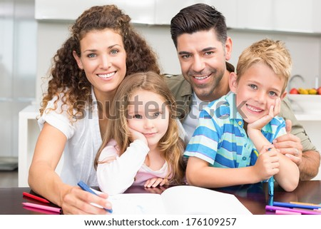 Parents colouring with their children at the table at home in kitchen - stock photo