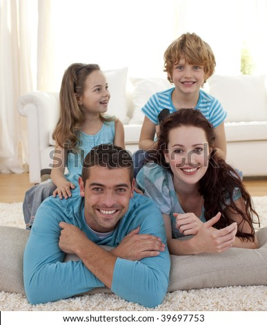 Parents, daughter and son lying on floor in living-room - stock photo