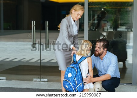 Parents encouraging their little daughter before the first day of school - stock photo