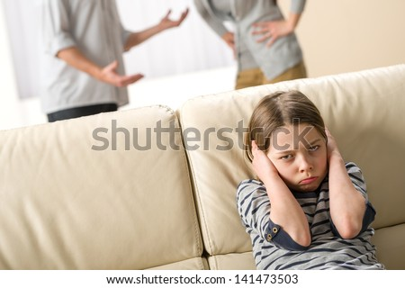 Parents fighting in front of their unhappy daughter child - stock photo