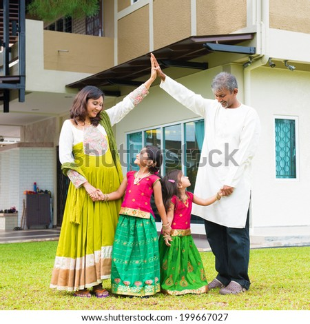 Parents forming  house roof shape above children. Beautiful Asian Indian family portrait smiling and standing outside their new house. - stock photo