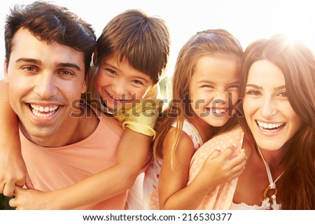Parents Giving Children Piggyback Ride In Garden - stock photo