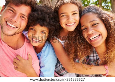 Parents Giving Children Piggyback Ride Outdoors - stock photo