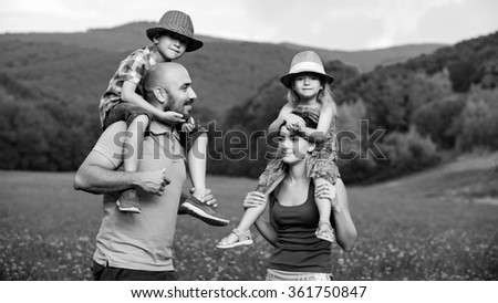 Parents giving piggyback ride to children, happy family time concept - stock photo