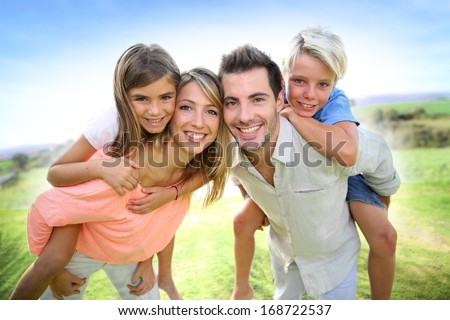 Parents giving piggyback ride to kids - stock photo