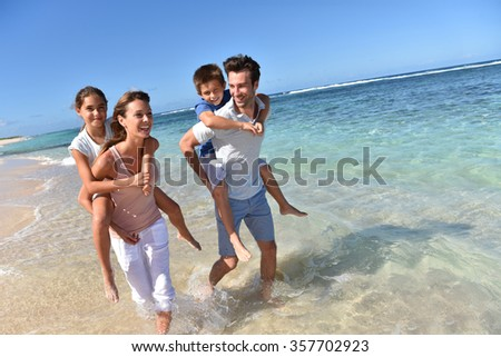 Parents giving piggyback ride to kids on a sandy beach - stock photo