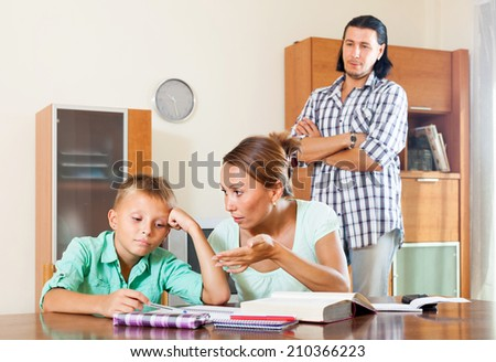 Parents  helping with homework in home interior - stock photo