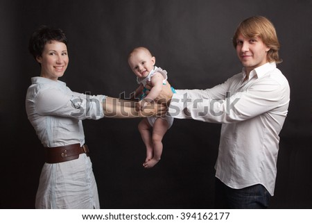 Parents hold their baby studio - stock photo
